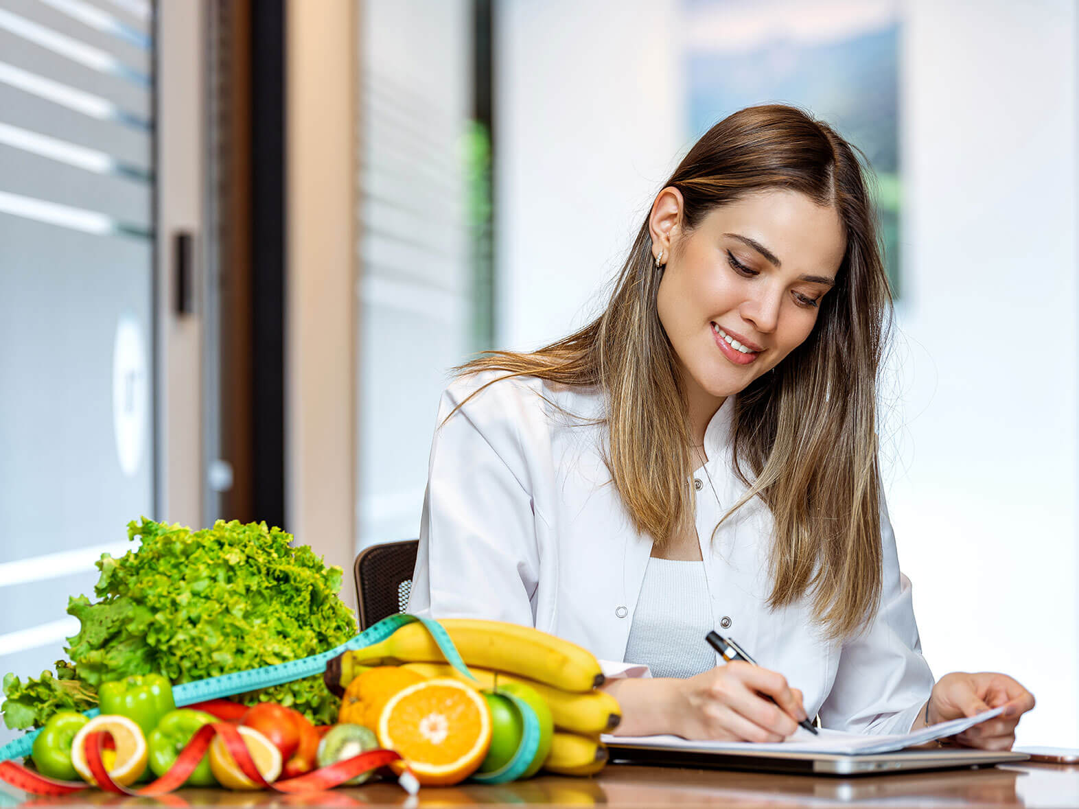 IBT Medicare Wellness | A dietician writing on a table with fruits and veggies.